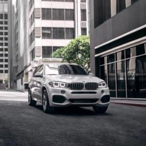 BMW white vehicle driving down street.
