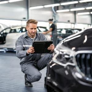 Service man with ipad completing an inspection of bmw vehicle.