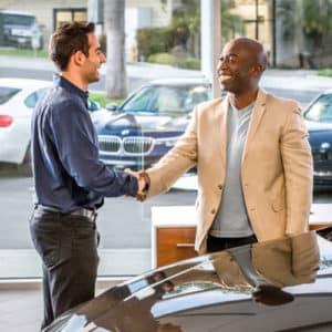 Two men shaking hands at Dealership.