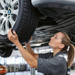 Service woman completing a tire alignment.