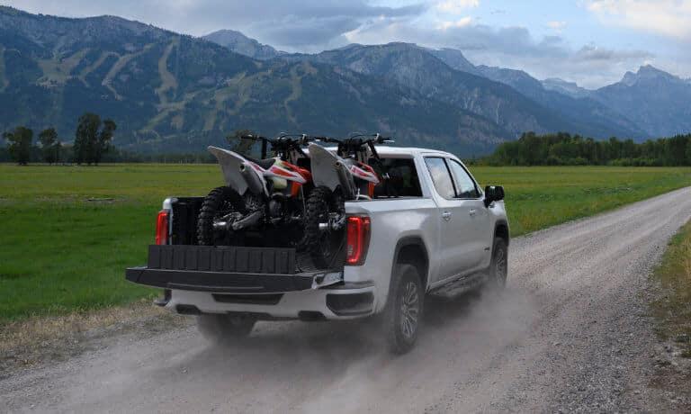 2021 GMC Sierra 1500 truck in white exterior towing motercross bikes