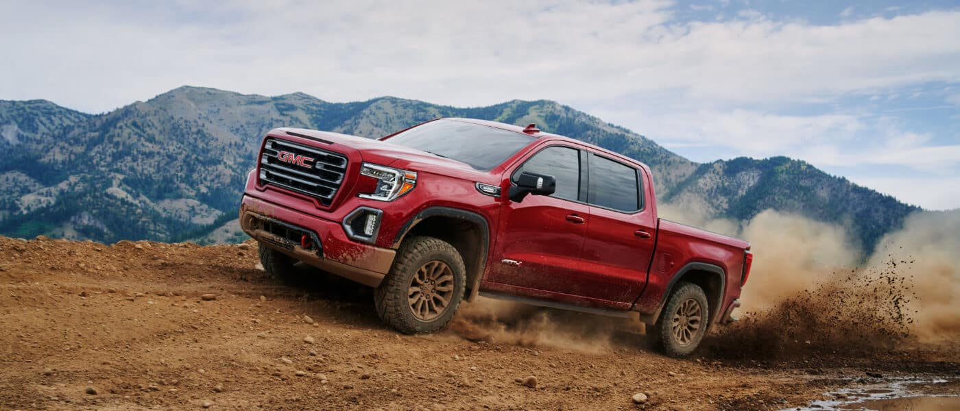 GMC Sierra 1500 in red exterior driving above dirt road