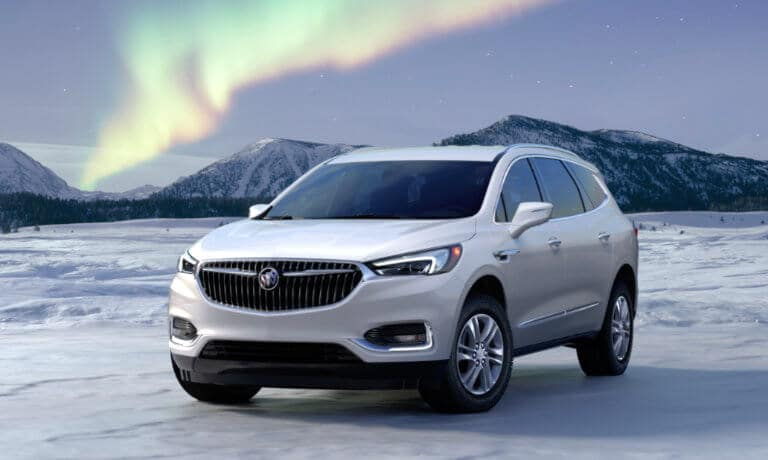 2021 Buick Enclave in white exterior beside snow and the Northern Lights