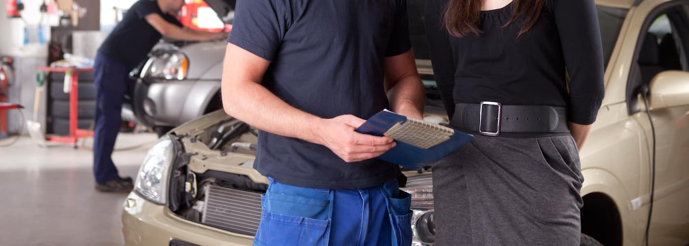 mechanic covering service bill with customer