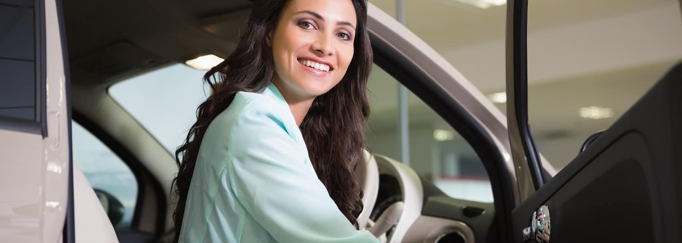 smiling woman sitting behind car steering wheel
