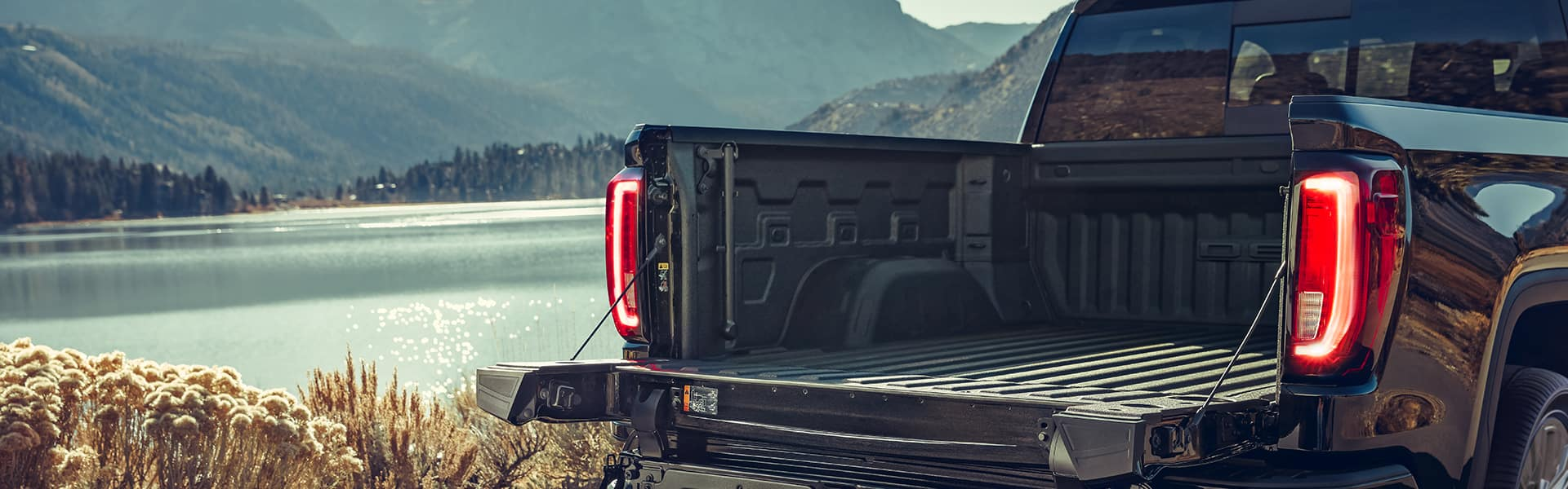 Performance features of the 2021 Sierra at Jack Giambalvo Buick-GMC of York | Open tailgate of the 2021 GMC Sierra parked by a lake