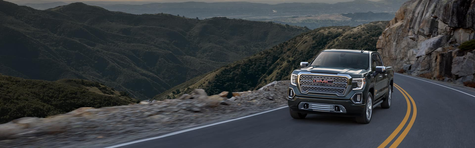 Performance features of the 2021 Sierra at Jack Giambalvo Buick-GMC of York | 2021 GMC Sierra driving through the Northern California hills