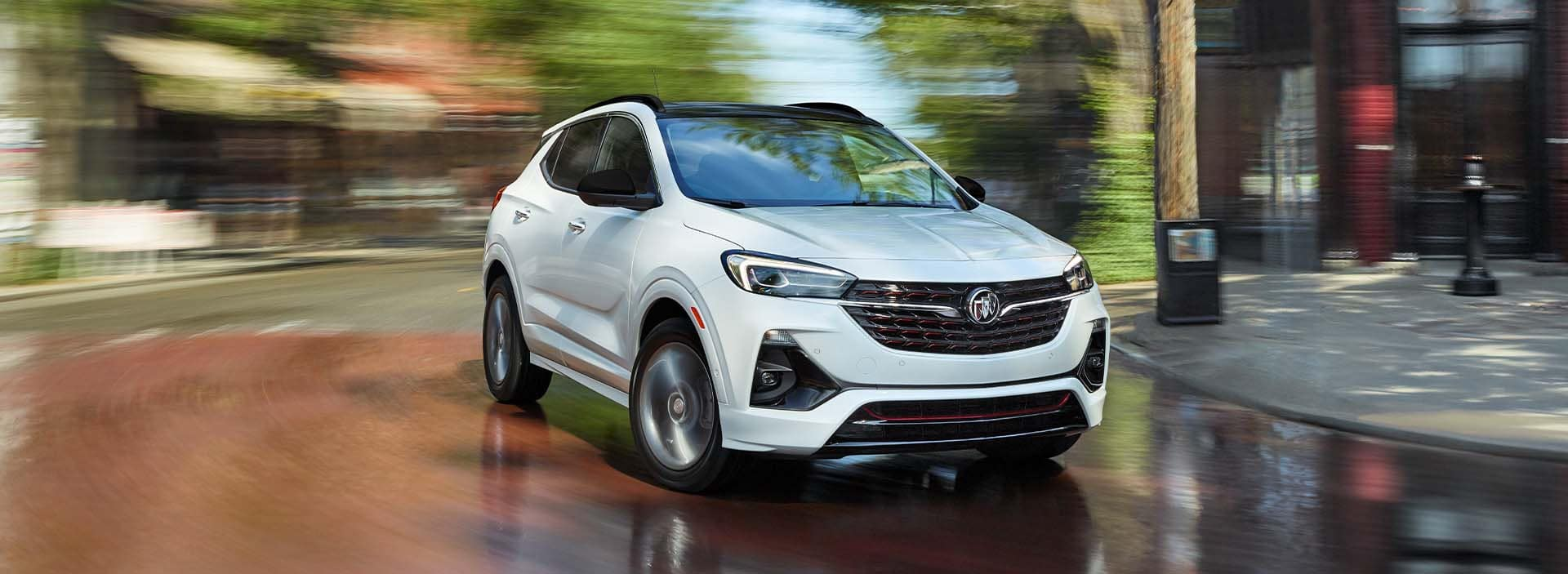 Model Features of the 2022 Buick Encore GX at Jack Giambalvo Buick-GMC | White 2022 Buick Encore GX Driving Quickly Around Bend in City Street