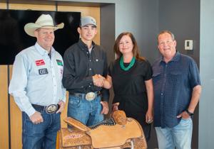 Megan Vance , VP of John Vance Auto Group, standing beside rodeo champion Clint Graves