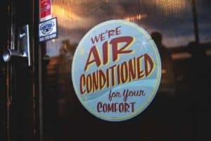 """a sign that says """"we're air conditioned for your comfort."""""""