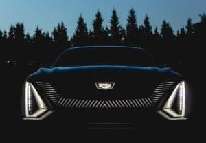 front of the new cadillac lyriq in edmond oklahoma with a dark forest background